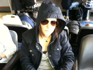 Lisa Lutz in airport wearing hood and sunglasses